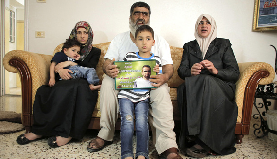 Son of Amer Abu Aysha holds his father's picture as he poses with his grandfather, grandmother and his mother for media in their house in the West Bank city of Hebron